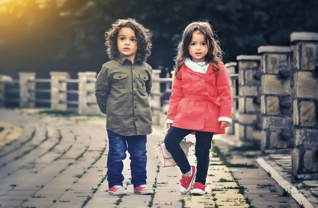 Two small children standing outside.