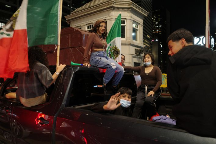 2 women and 2 men in back of pick up adorned with mexican flags held by 2 other women.