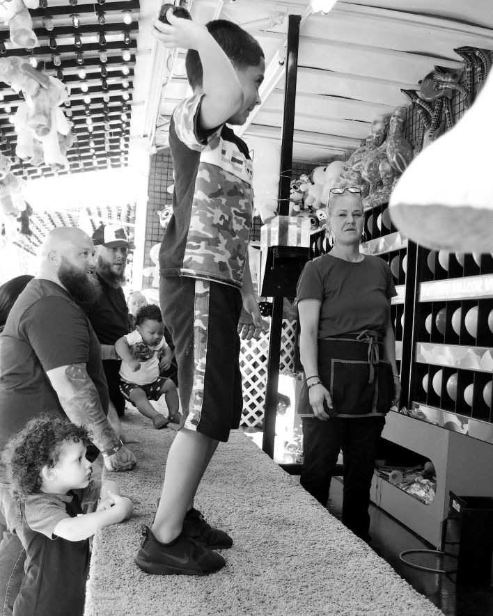 Little boy about to throw a ball in a carnival arcade contest while adults watch.