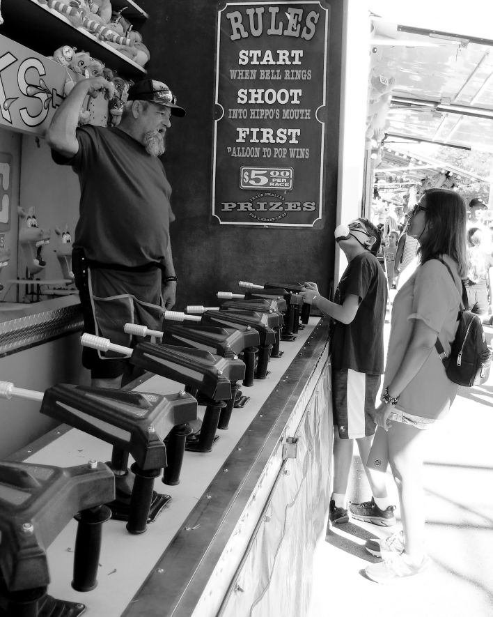 Carnival worker explaining rules of an arcade game to a mother and her child.