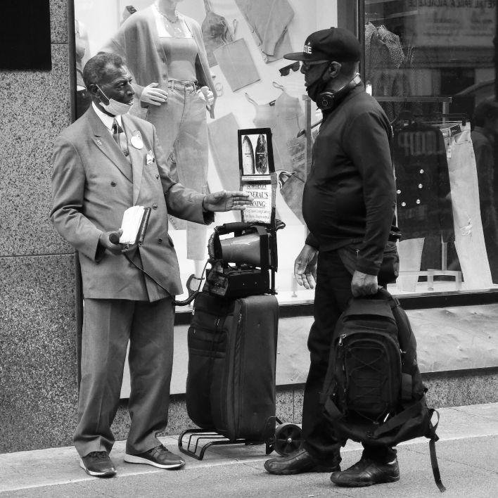2 men speaking respectfully. 1 has a suit and a bible and a bullhorn, the other has headphones and a backpack.