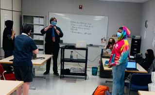 Teacher demonstrating how to tie a necktie for students preparing for job interviews