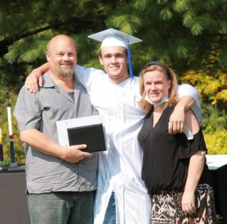 2020 Graduating Student with his smiling Parents