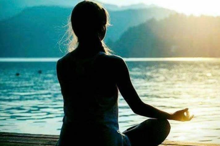 A woman facing the mountains and water at sunset in a Namaste yoga position